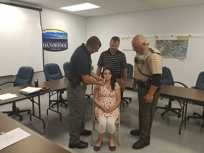 White Pine Police Chief Chad Cotter is joined by Dandridge Police Department's Detective Sgt. Kenneth Lodwick and THP Sgt. Jeff Coffey, who is demonstrating  administering NARCAN to an overdose patient, played by Raven Mason.Photo submitted by Debra Shultz