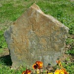 Original, rough-hewn gravestone on the grave of Patriot James McCuistion.  The new gray granite marker will lie flat over the grave and honor his service in the Revolutionary War.